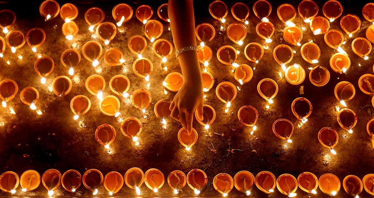 A devotee lights oil lamps
